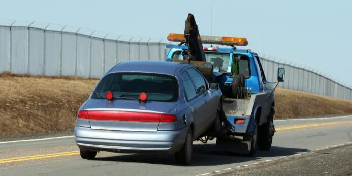 Towtruck Towing On Road With Fence